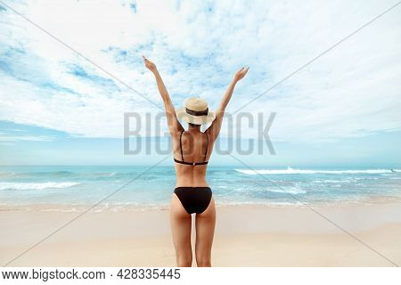 Portrait Beautiful Young Woman In Bikini With Raised Hands, Looking At Ocean. Rear View Of Girl. Fre