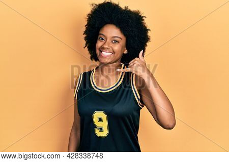 Young african american woman wearing basketball uniform smiling doing phone gesture with hand and fingers like talking on the telephone. communicating concepts.
