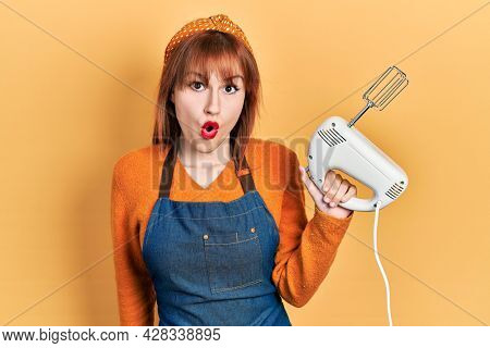 Redhead young woman holding pastry blender electric mixer scared and amazed with open mouth for surprise, disbelief face