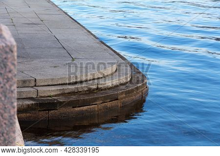 Granite Embankment Of The Neva River With A Stone Platform With Steps For Descending To The Water. O