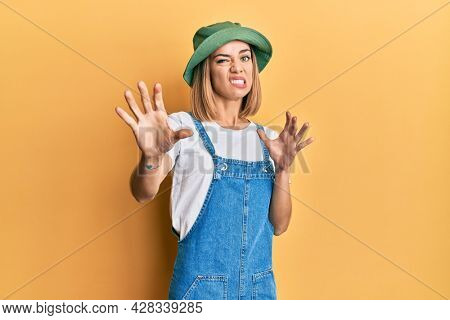 Young caucasian blonde woman wearing denim jumpsuit and hat with 90s style disgusted expression, displeased and fearful doing disgust face because aversion reaction. with hands raised
