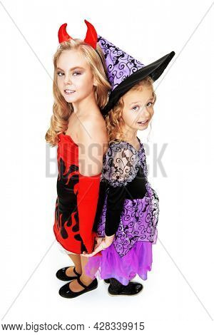 Two happy girls in costumes of a witchs are smiling on a yellow background. Halloween celebration. Fancy dress costumes for children.