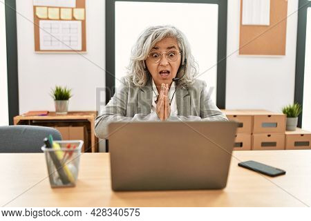 Middle age businesswoman sitting on desk working using laptop at office begging and praying with hands together with hope expression on face very emotional and worried. begging.