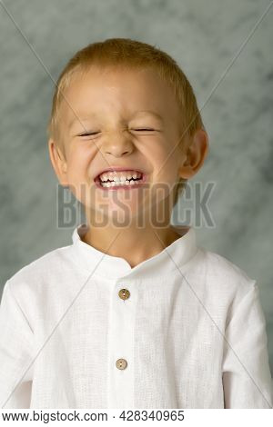 Emotional Portrait Of A Positive And Happy Little Boy Smiling With Closed Eyes. He Closed His Eyes A