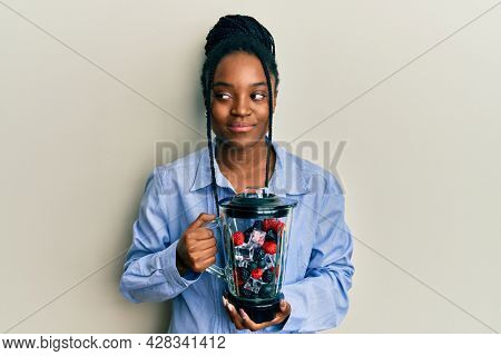 African american woman with braided hair holding food processor mixer machine with fruits smiling looking to the side and staring away thinking.