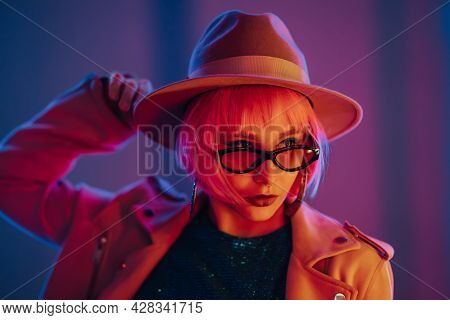 Eccentric Woman With Pink Hair Posing Under Neon Light. Charming Unusual Girl In Hat And Sunglasses,