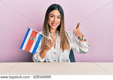 Young hispanic woman holding costa rica flag sitting on the table smiling happy and positive, thumb up doing excellent and approval sign