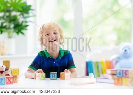 Child Learning Letters And Numbers. Kid With Colorful Wooden Abc Blocks. Little Boy Spelling Words W