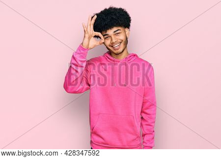 Young african american man with afro hair wearing casual pink sweatshirt smiling positive doing ok sign with hand and fingers. successful expression.