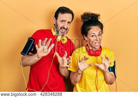 Middle age couple of hispanic woman and man wearing sportswear and arm band disgusted expression, displeased and fearful doing disgust face because aversion reaction. with hands raised