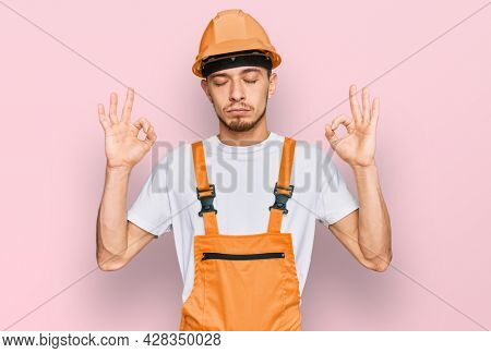 Hispanic young man wearing handyman uniform and safety hardhat relax and smiling with eyes closed doing meditation gesture with fingers. yoga concept.