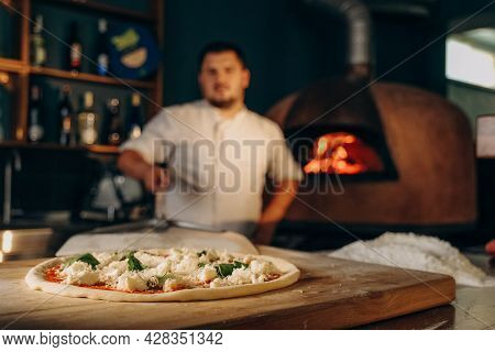 The Chef Prepares Pizza In A Wood-fired Oven. Cooking Pizza. The Cook Puts The Pizza In The Oven.