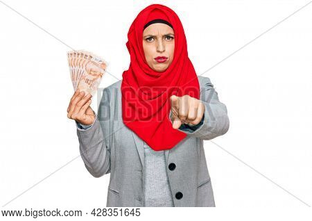 Beautiful hispanic woman wearing islamic hijab holding turkish lira banknotes pointing with finger to the camera and to you, confident gesture looking serious