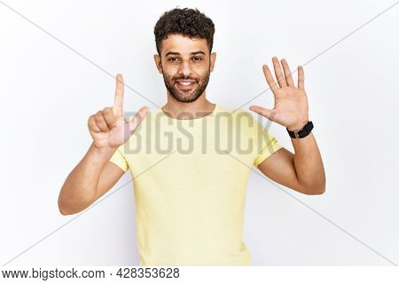 Arab young man standing over isolated background showing and pointing up with fingers number seven while smiling confident and happy.