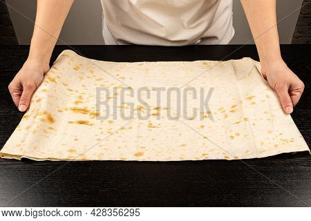 Female Hands Lay Out Fresh Pita Bread For Making Shawarma On The Background Of A Black Wooden Table