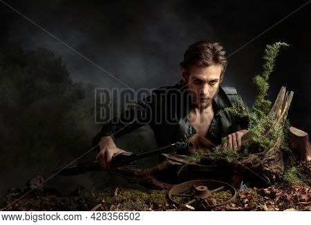 Portrait Of A Young Man With A Rifle. A Serious Man In A Black Leather Jacket With A Rifle Looks Men