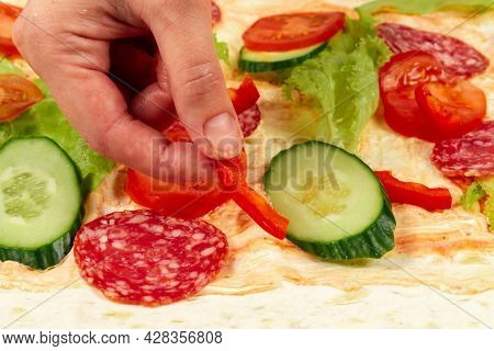 Female Hand Puts Fresh Chopped Vegetables On Unwrapped Shawarma With Sauce, Cucumber, Lettuce And Sa