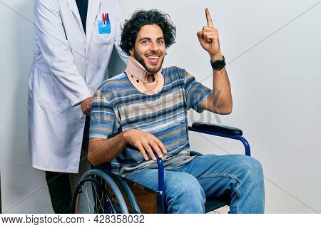 Handsome hispanic man sitting on wheelchair wearing neck collar pointing finger up with successful idea. exited and happy. number one.