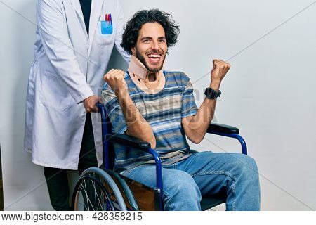 Handsome hispanic man sitting on wheelchair wearing neck collar celebrating surprised and amazed for success with arms raised and open eyes. winner concept.