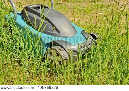 Professional Electric Lawn Mower While Mowing A Grass And Lawn. Garden Lawn Mowing, Professional Car
