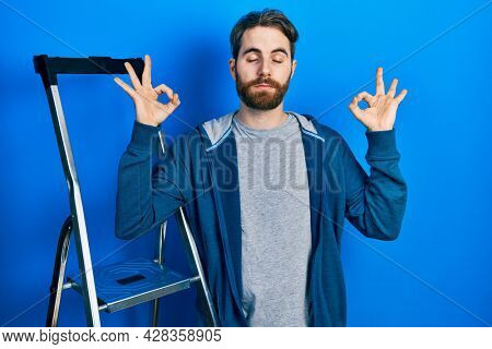 Caucasian man with beard by ladder relax and smiling with eyes closed doing meditation gesture with fingers. yoga concept.