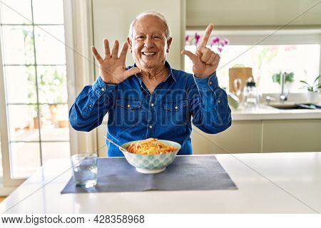 Senior man with grey hair eating pasta spaghetti at home showing and pointing up with fingers number seven while smiling confident and happy.