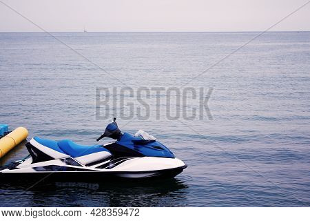 Jet Ski White And Blue On The Pier By The Sea.