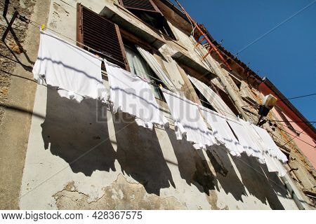 Laundry Hanging On A Clothes Line On An Old City Building. Hanging Laundry And Walls. Washing Hangin