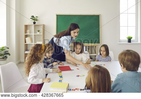 Portrait Of Diligent Schoolkids And Teacher Studying Talking At Lesson