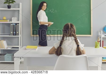 Schoolkid Sitting At Desk And Listening Attentively To Teacher In Modern Classroom