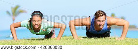 Happy people doing push-ups during yoga class at outdoor beach park on grass. Panoramic banner of Asian woman and man instructor training arms muscles outside.