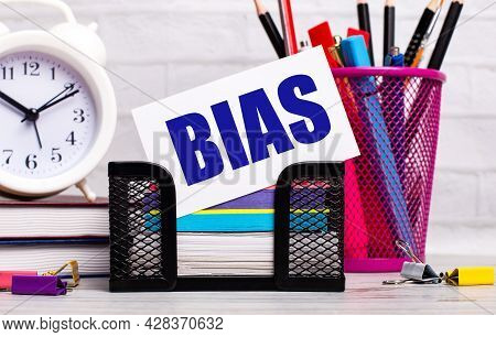The Office Desk Has Diaries, An Alarm Clock, Stationery, And A White Card With The Text Bias. Busine