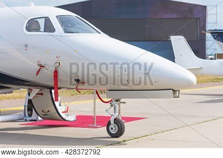 Business Jet With Open Door And Red Carpet, View Of The Nose And Cockpit Of The Airplane
