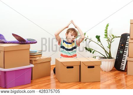 Happy Boy Having Fun During Moving Day To A New House. Housing For Young Family With Children. Famil