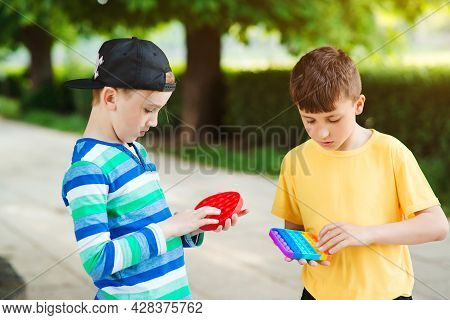 Cute Boys Playing With Trendy Pop It Toy. Friends On A Walk With Silicon Bubble Toys. Boys Having Fu