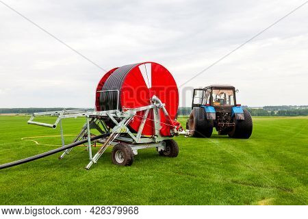 Watering A Vegetable Green Field With A Big Water Hose On The Red Bobbin Near Blue Tractor In Summer