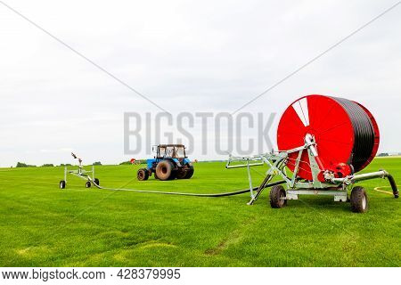 Watering A Vegetable Green Field With A Big Water Hose On The Red Bobbin, Sprinkler And Blue Tractor