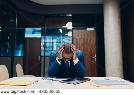 Sad African American Black Businessman Sit And Hold Head With His Hands At Office Table. Business Pe