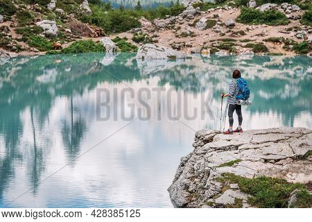 Backpacker Woman With Backpack And Trekking Poles Enjoying The Turquoise Lago Di Sorapiss 1925m Alti