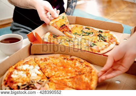 Close Up People Hands Taking Slices Of Pizza From Pizza Box. Friends Eating Pizza Together. Food Del