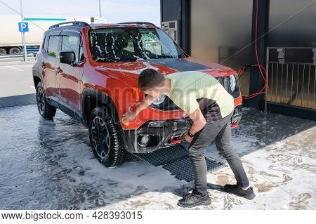 The Teenager Washes The Car Outdoors. Car In Foam, Manual Car Wash