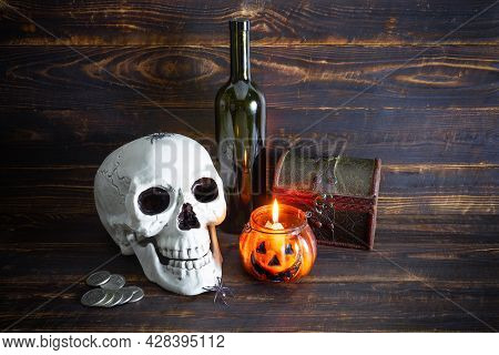 Human Skull, Dark Glass Bottle, Coins, Casket And Burning Candle In Glass Candlestick In The Form Of