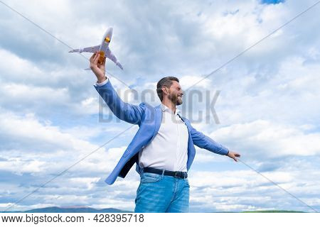 Confident Happy Man Businessperson In Jacket Hold Toy Plane On Sky Background, Business Success
