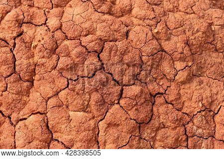 Soil Erosion. Cracks In Red Clay Ground. Arid Climate. Dry Dewatered Sandy Earth. Abstract Texture O