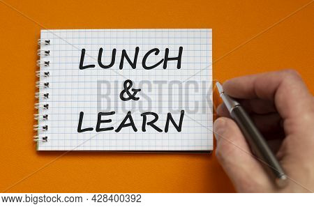 Lunch And Learn Symbol. Businessman Writing Words 'lunch And Learn' On White Note. Beautiful Orange