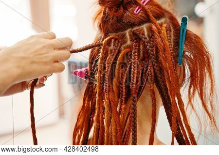 Braiding Process African Plaits With Colored Kanekalon. Hairdresser Weaves Woman Ginger Dreadlocks.