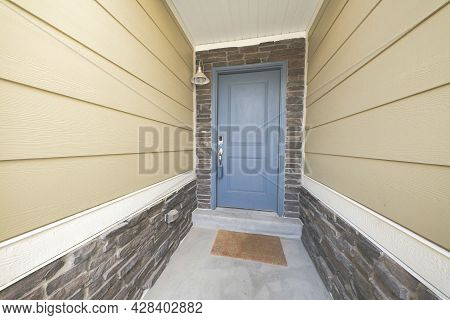 Covered Front Door With Bluish Gray Front Door And Stone Bricks Wall Siding