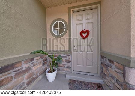 Front Door Exterior With Red Heart-shaped Display At The Front And A Decorative Doormat At The Floor