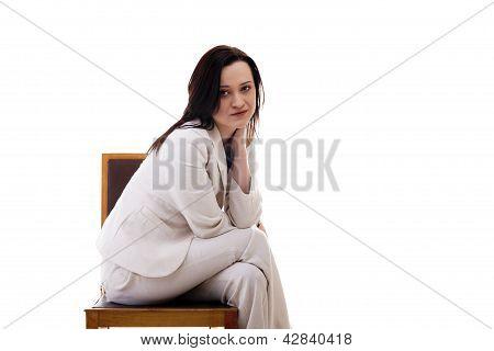 Beautiful Businesswoman In A White Suit Sitting On A Chiar Isolated On White