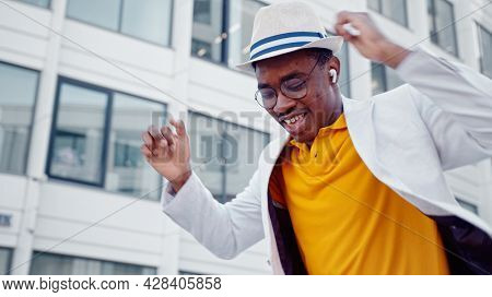 African American man in hat and wireless headphones listens to music and dances with joyful smile on megalopolis street close view